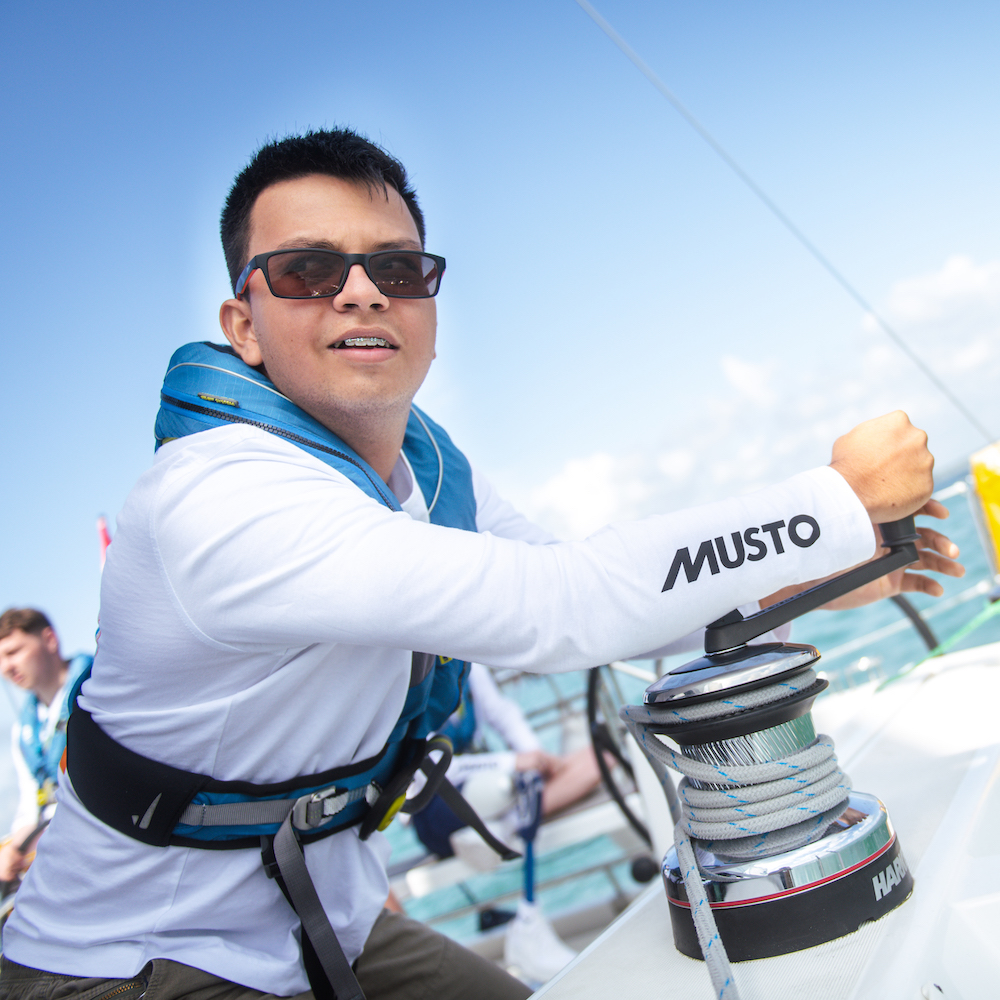 Young person winching on a yacht with clear Musto logo on their sleeve