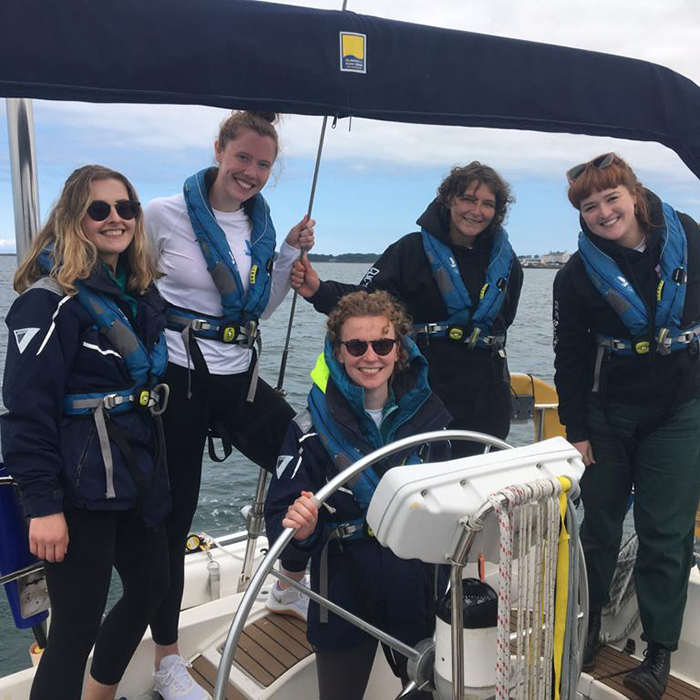 Five young women at the helm of a yacht are smiling at the camera, four of whom are young people being supported by the Trust and one is Laura, a volunteer, who works for Young Lives vs Cancer