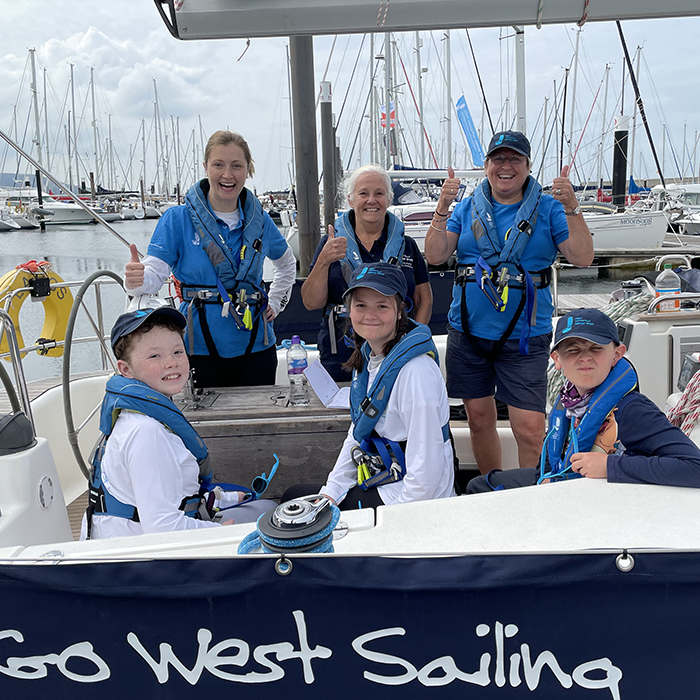 Three young people are smiling at the camera on board a yacht, with three members of the Trust team smiling behind them