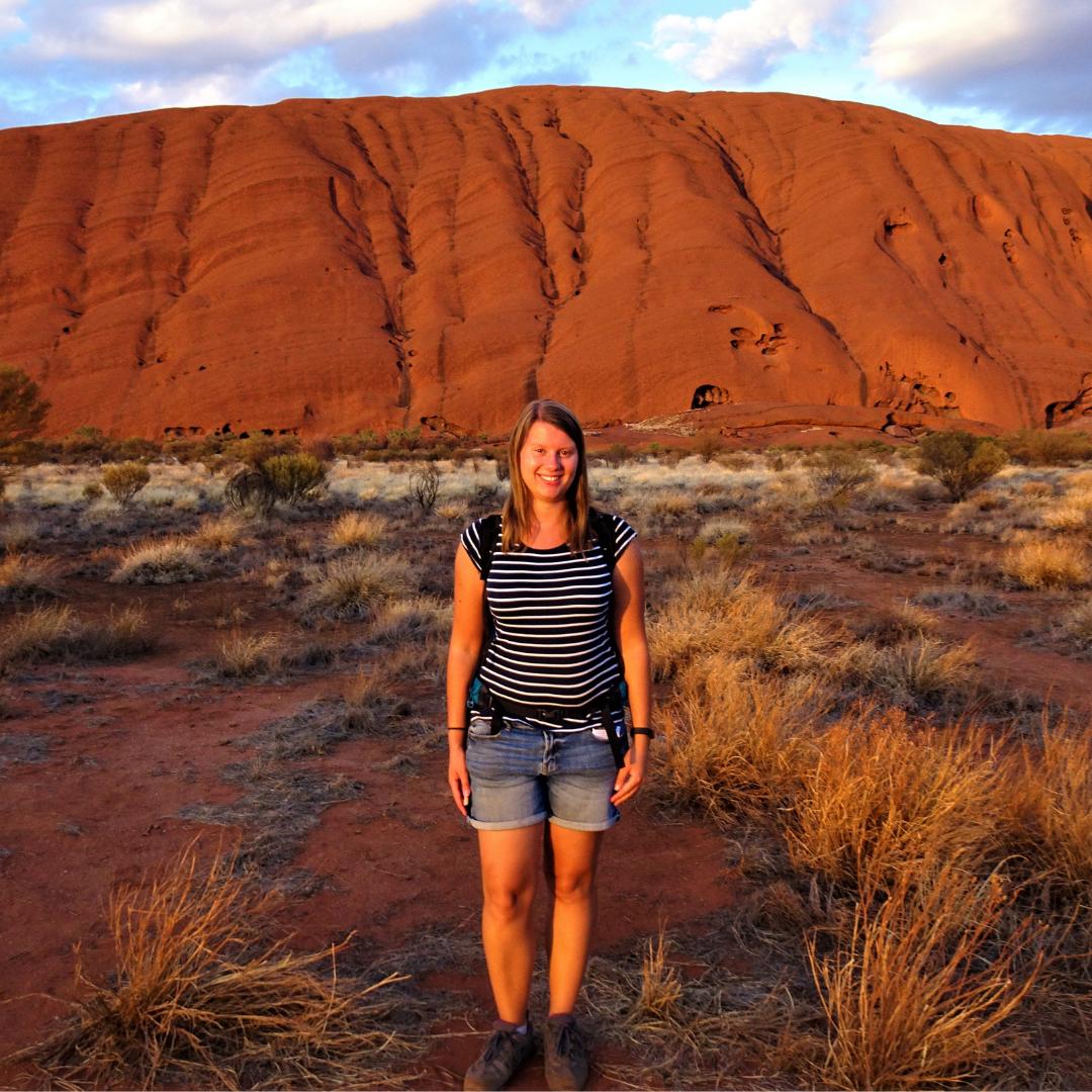 Rachel Blackford standing in front of Aires Rock in Australia