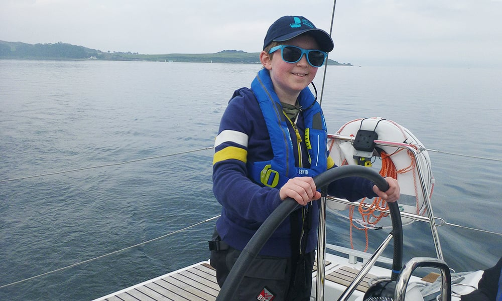 Finn at the helm of a boat with sunglasses and baseball cap on