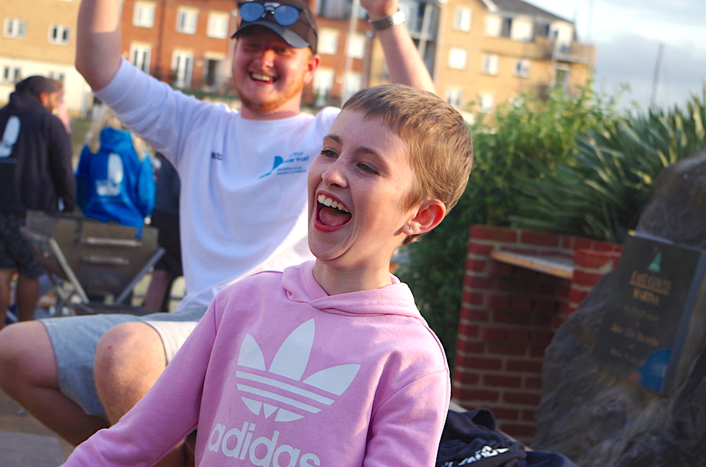 <p>Girl in pink hooded sweatshirt laughing at BBQ in Cowes</p>