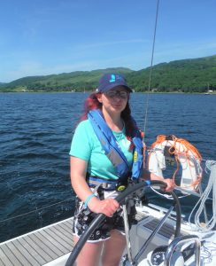 Katie Holland helming on her first Trust trip in Largs last summer